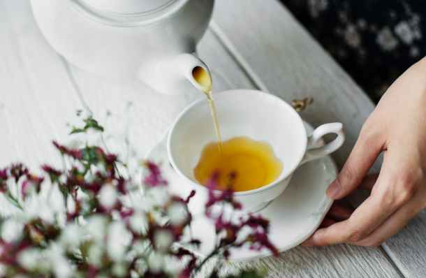 person pouring tea on teacup
